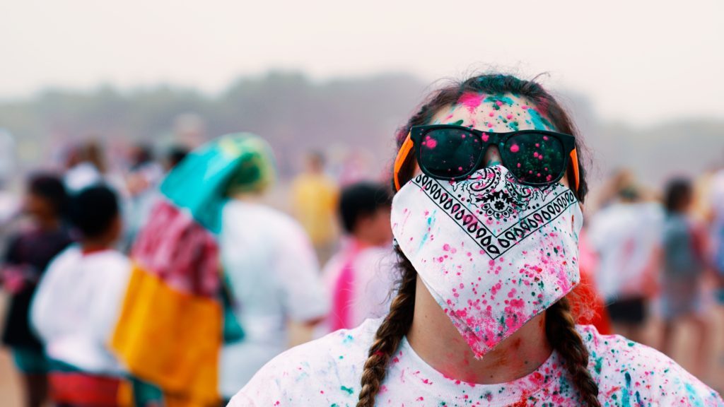 A woman wearing sunglasses and covering her face with a bandana during a painting fiesta