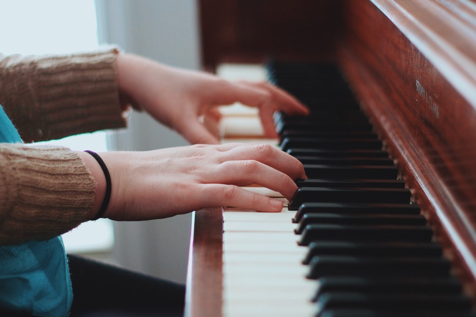 A pianist is sitting at a piano and playing a song.