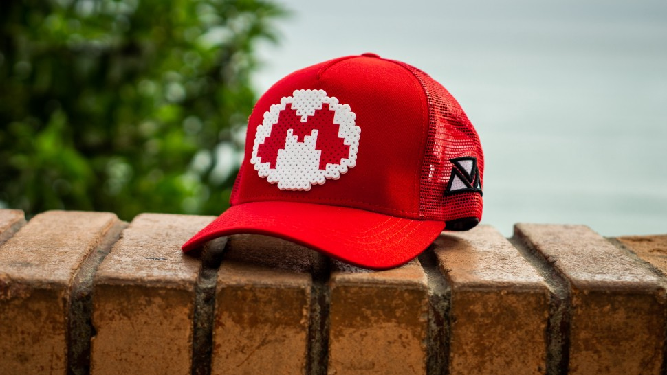 A red baseball hat has a Mario logo on the front of the hat.