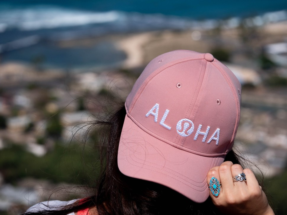 A woman is wearing a pink baseball hat with the words