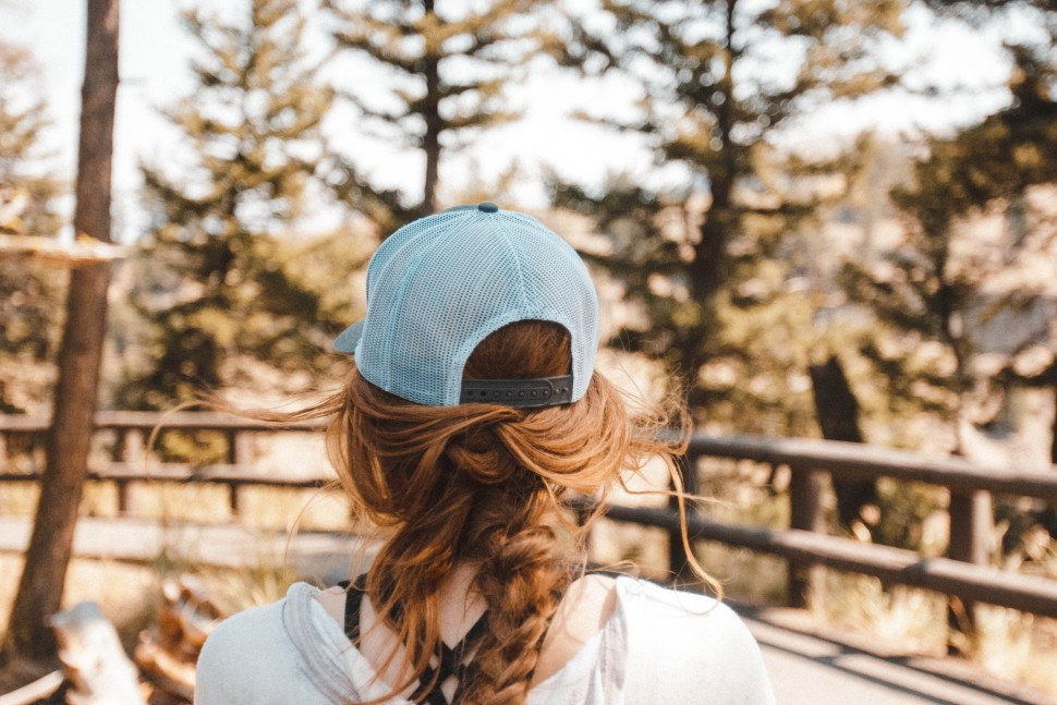 A woman facing away from the cameria wearing a blue baseball cap