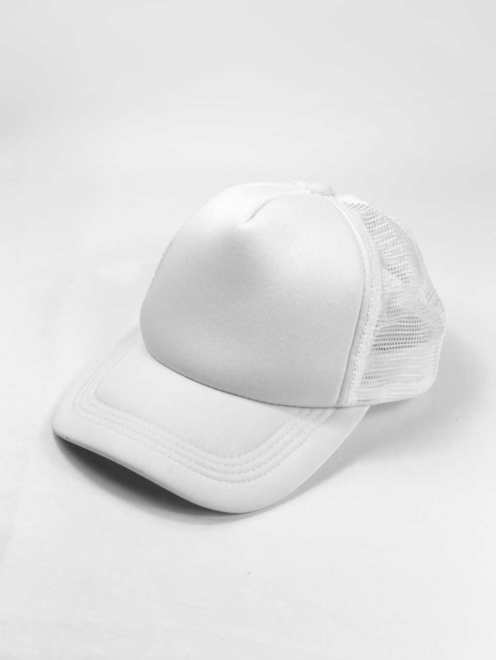A plain, white trucker hat sits in front of a white background and is one of the best caps for men.