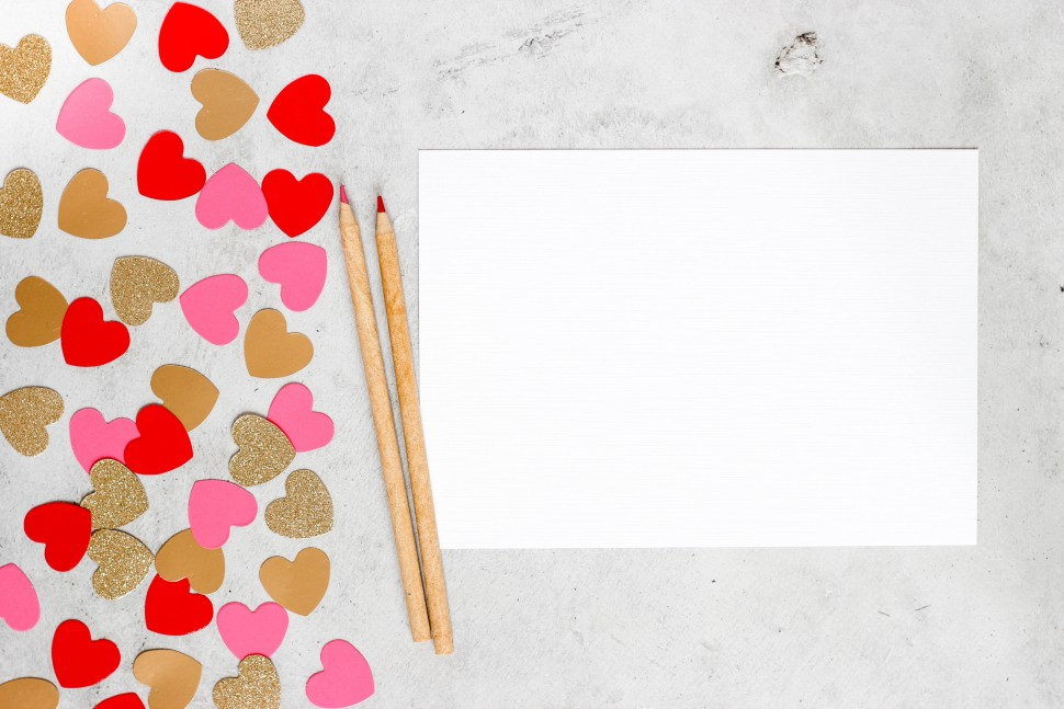 Piece of paper with two pencils and cut out hearts next to it.