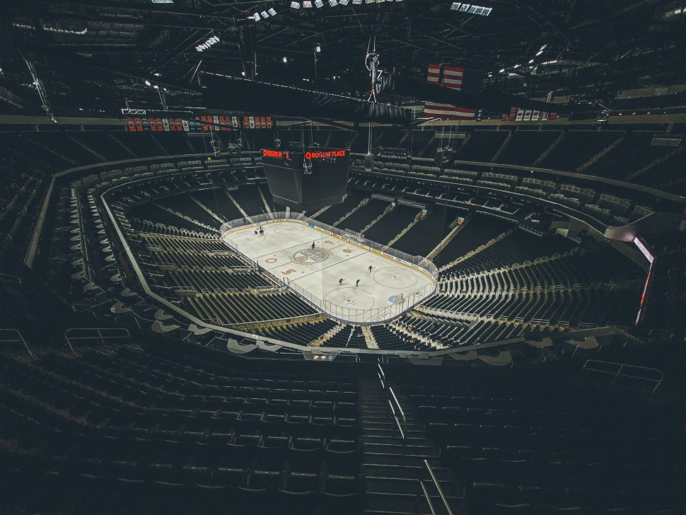 Empty stadium with hockey players in the middle on the ice rink.