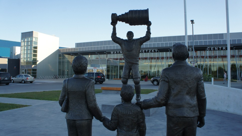Statue of Wayne Gretzky holding the Stanley cup in front of a statue of fans.