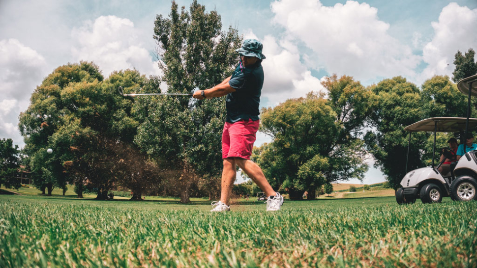 A man swings a golf club while wearing a bucket hat which is one of the best hats for golfon a golf course.
